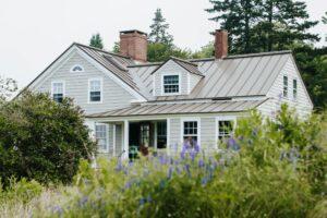 a grey home behind a garden